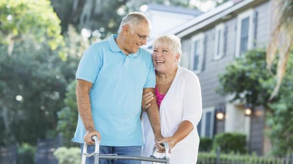 Senior couple walking in neighborhood, man with walker