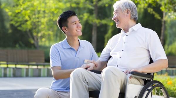 Wheelchair bound man with nursing assistant