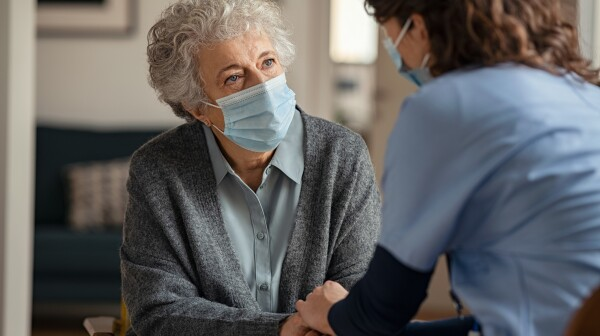 Female doctor consoling senior woman wearing face mask during home visit