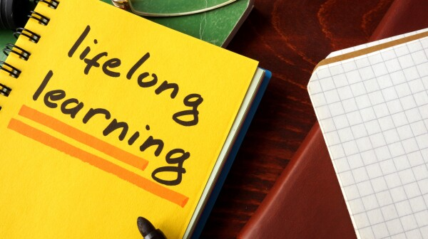 Notebook with lifelong learning  sign on a table.