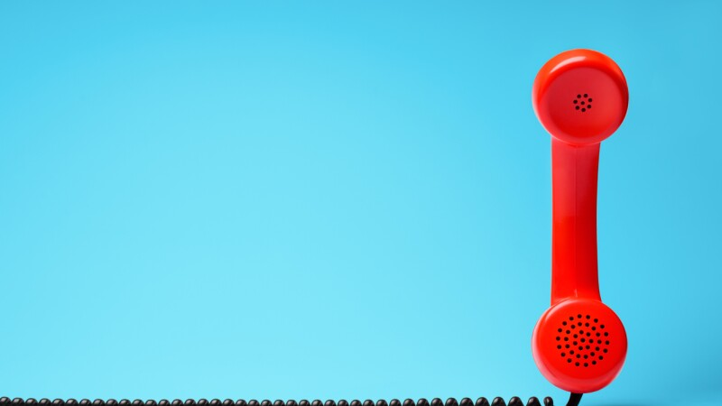 Red telephone in retro style on blue background.