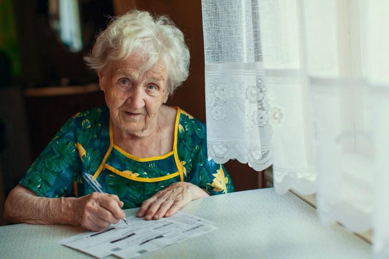 MONEY_elderly woman paying bills_DimaBerkut