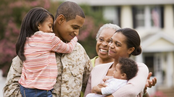 African American military father hugging family