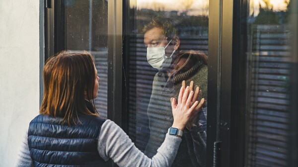 Woman looking at masked husband quarantined behind window