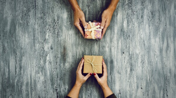woman and man exchanging gifts