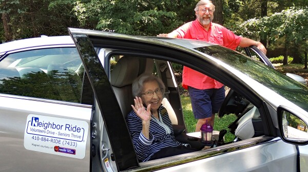 Caregiver holding wheelchair in the car for disabled elderly woman with walking stick