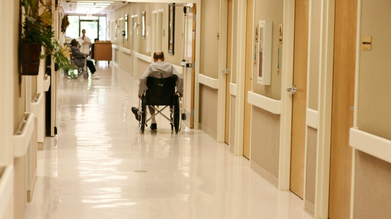 A man in a wheelchair in a nursing home hallway