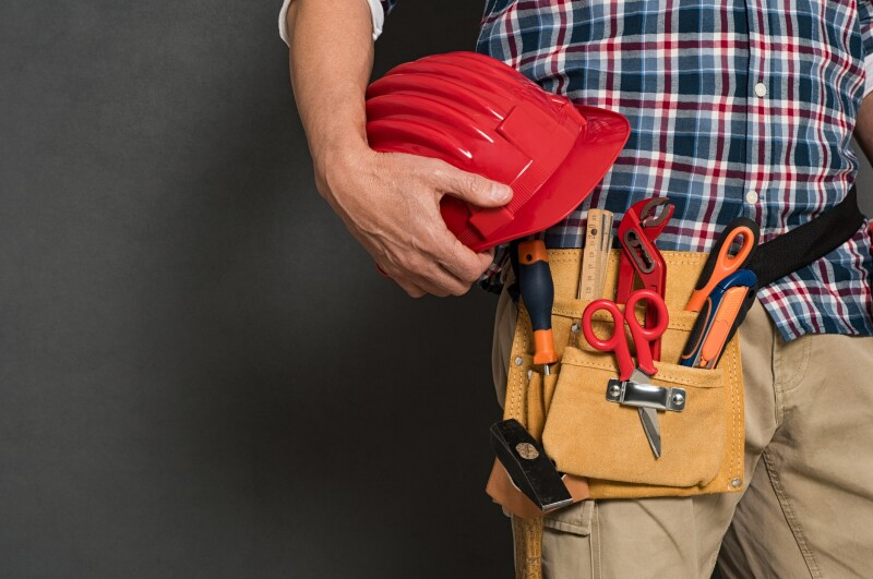 Worker holding hardhat and toolkit