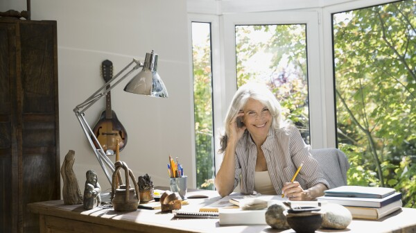 Portrait of senior woman writing in home office