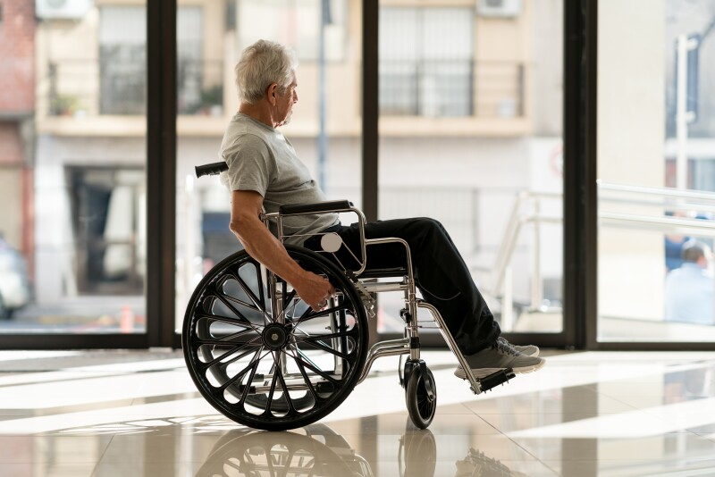 Disabled senior man at a nursing home looking away to the door