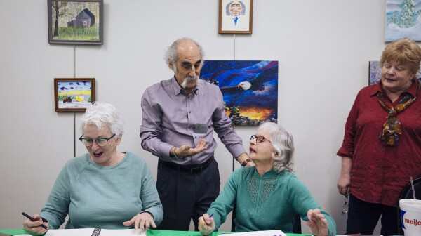 A man speaks with three women at an art class