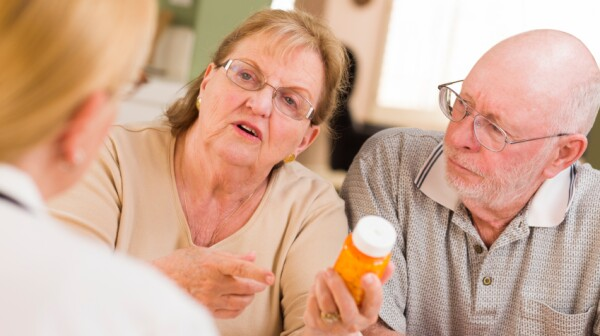 Doctor or Nurse Explaining Prescription Medicine to Attentive Senior Couple.
