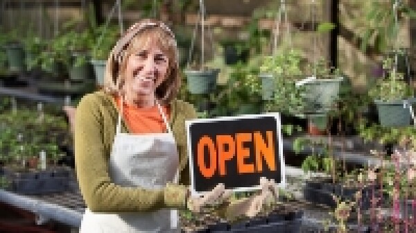 Small business owner, mature woman (50s), holding OPEN sign in plant nursery.