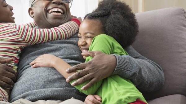 Older man hugging grandchildren on sofa