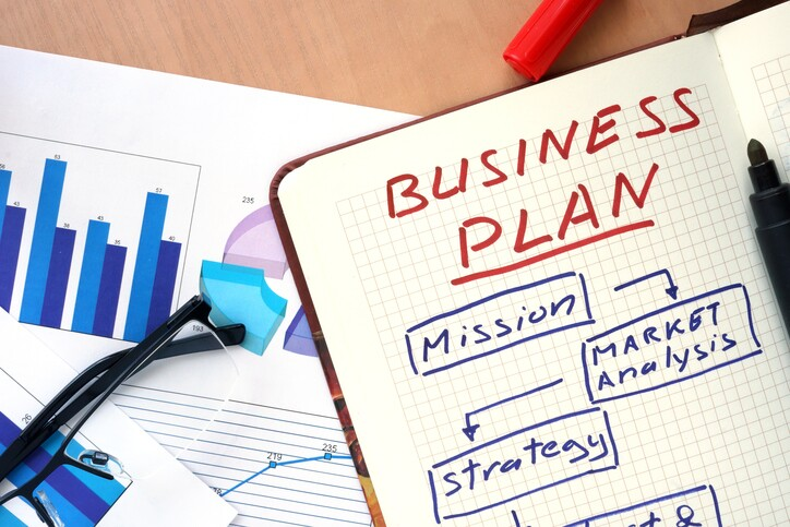 Notepad with words business plan  concept and glasses.