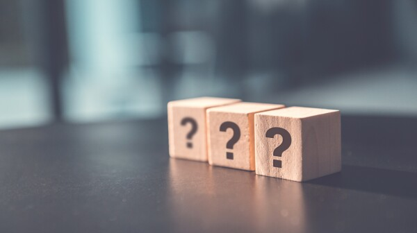 ? Questions Mark word in wooden cube block on table background. FAQ  Answer, Q&A.