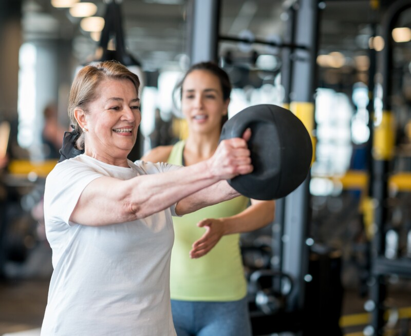 Happy adult woman exercising at the gym with her coach