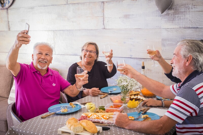 group of elderly men and women at home eating with fun