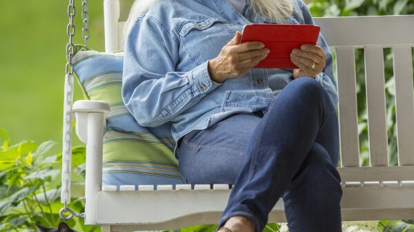 Caucasian woman using digital tablet on porch swing
