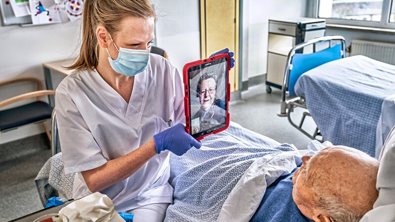 A nurse wearing a face mask holds up a tablet to a man in a nurs