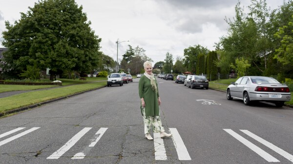 An older woman stands in a crosswalk