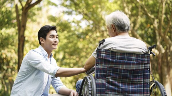 asian son comforting wheelchair bound father image .jpg
