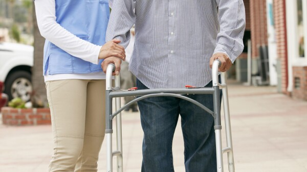 Assisting a senior man with using his walking frame