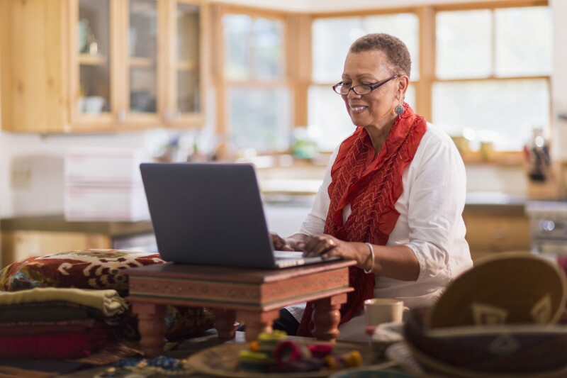 Older mixed race woman using laptop in home office