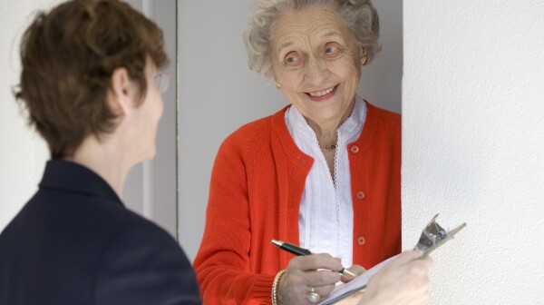 Smiling senior woman at her door signing a document on a clipboard held by a woman