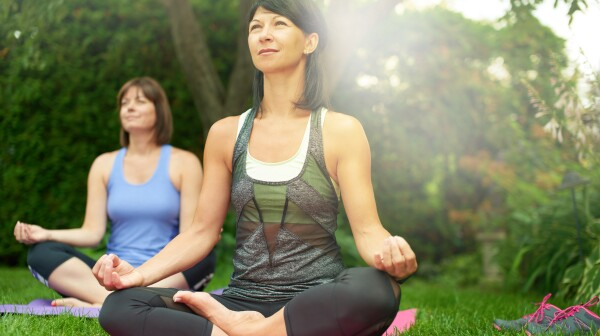 Two mature women keeping fit by doing yoga in the