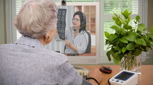 An older woman speaks to a medical professional via video chat