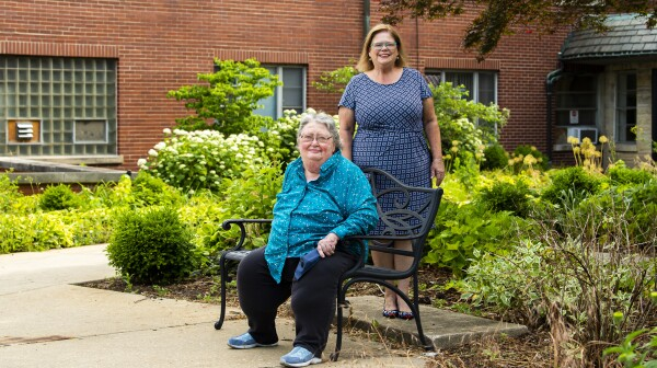 Two women outside of a senior-living facility