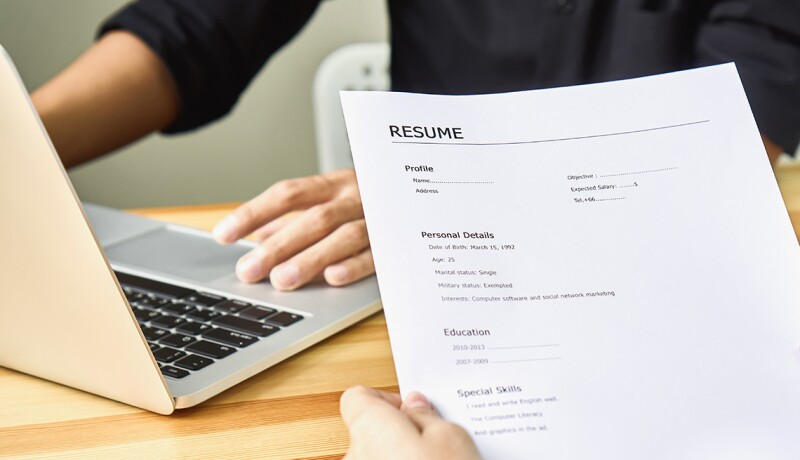 Cropped Image Of Person Holding Resume Against Business Person Using Laptop At Table