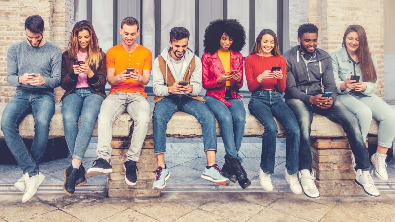 Group of multiracial young people sitting outdoors and watching down to his smartphones