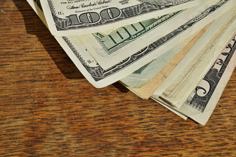 Heap of American money (US currency, USD) on wooden background