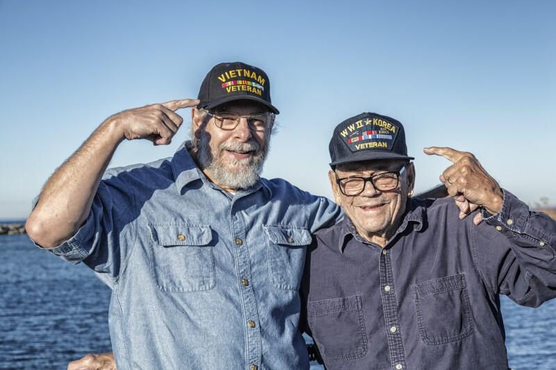 Two USA Military War Veterans Pointing At Souvenir Hats