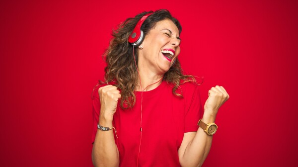 Middle age senior woman wearing headphones listening to music over red isolated background very happy and excited doing winner gesture with arms raised, smiling and screaming for success. Celebration concept.