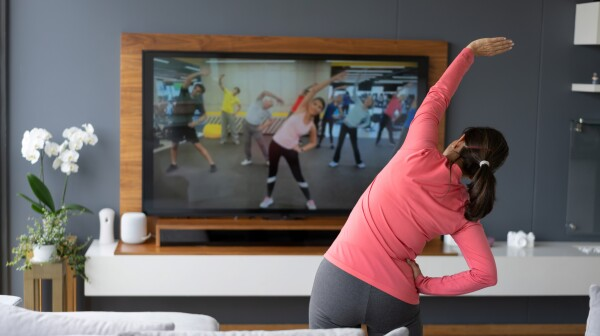 Back view of senior woman following an online stretching class looking at TV screen