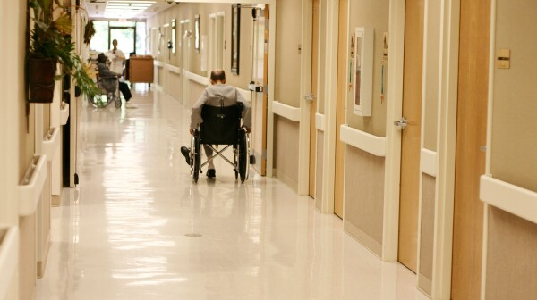 A man in a wheelchair in a nursing home hallway