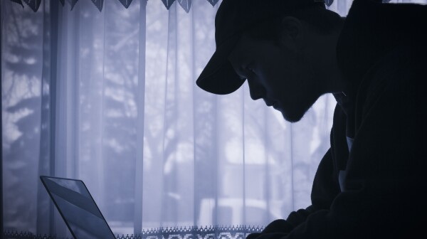 silhouette image of young man on his laptop.