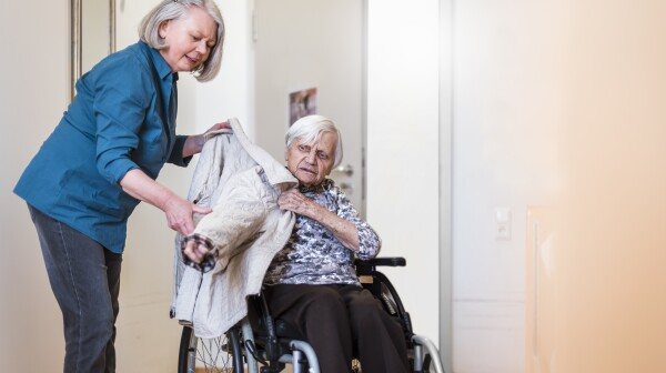 Woman taking care of old woman in wheelchair putting her jacket on