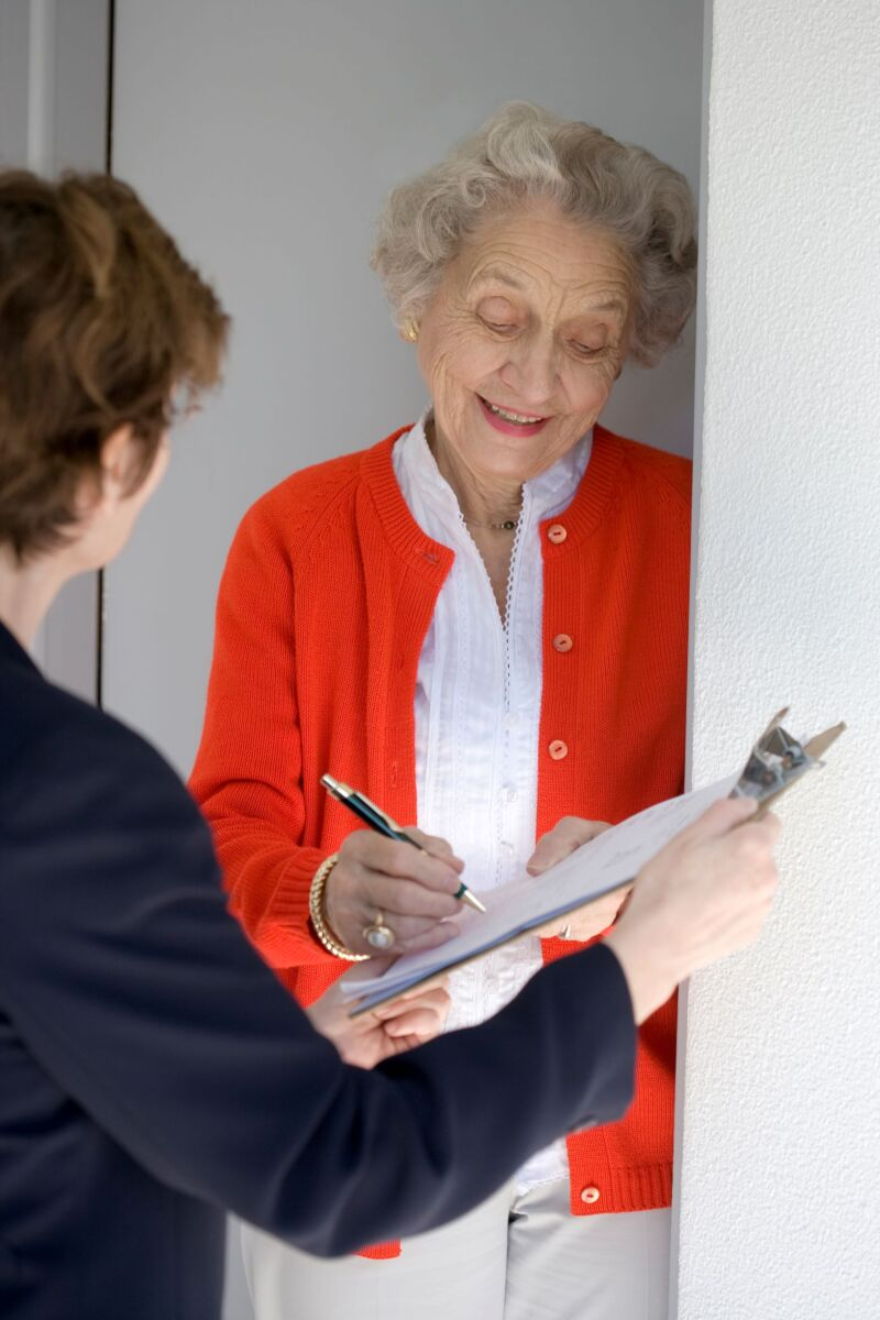 Smiling senior woman completing form