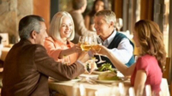 Four mature adults toasting with white wine in restaurant, smiling