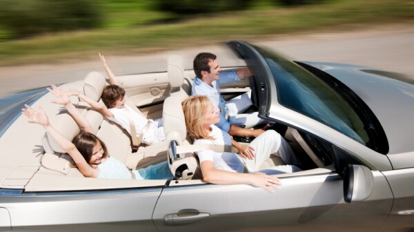 Happy family driving in a convertible car.