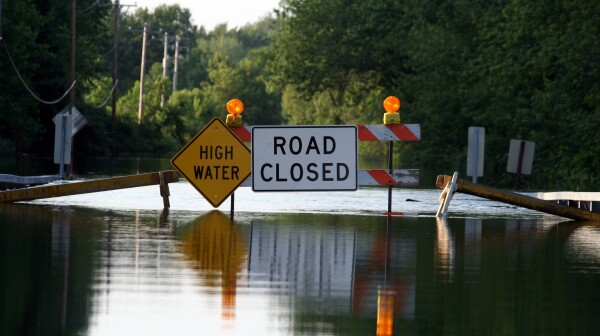 A road closure signage as water covers the road