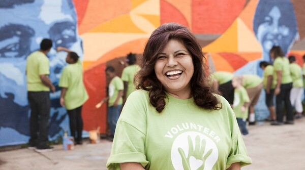 A woman smiles while a group of community volunteers paint a wal