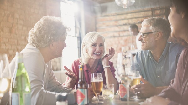 Couples talking and drinking beer at restaurant table