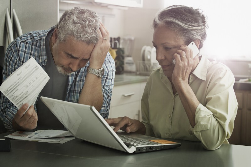 Stressed Hispanic couple paying bills on laptop