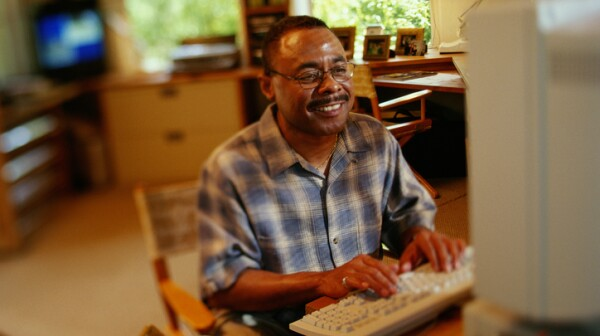 MAN ON COMPUTER AT HOME, AFRICAN AMERICAN