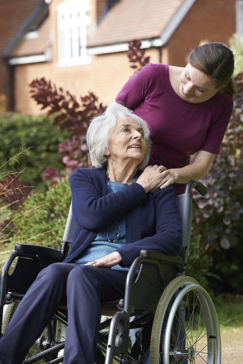 Daughter Pushing Senior Mother In Wheelchair